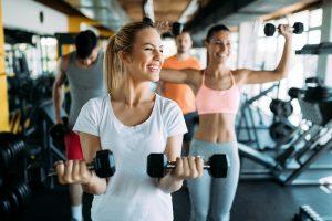 Mulheres sorrindo fazendo exercício com peso na academia.