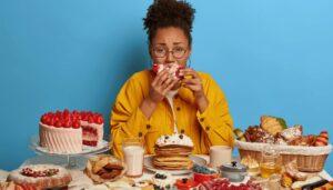 mulher comendo bolos e doces