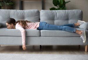 Mulher deitada no sofá sem fazer atividade física - Magnus