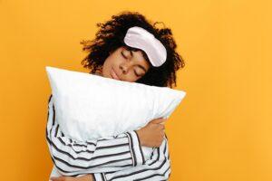 Dormindo. Sonhos. Retrato de mulher. Garota afro-americana de pijama abraçando um travesseiro, sobre um fundo amarelo